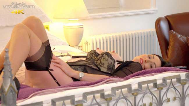 Miss Hybrid suspender twanging in seamed stockings on the bed.