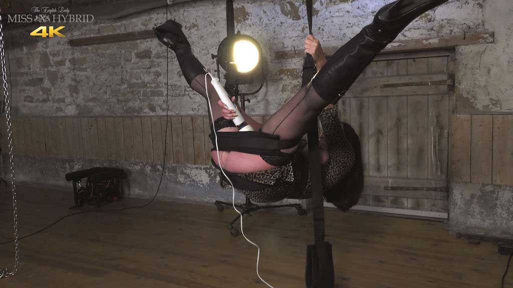 Dungeon sex swing and legs open in seamed stockings and boots.