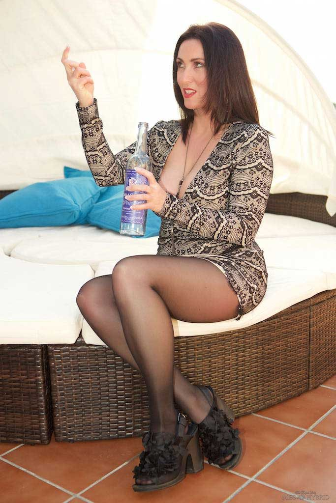 Miss Hybrid sexy long leags and huge cleavage playing with a bottle.