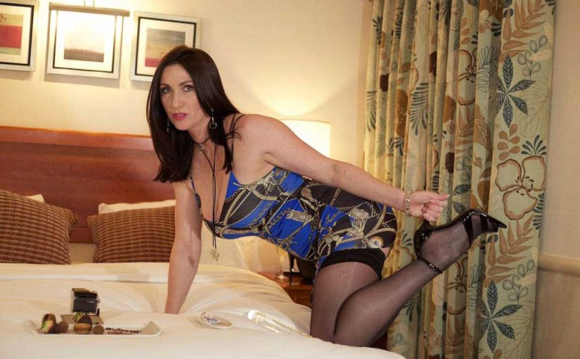 Miss Hybrid stiletto heels and nylons filming herself on the bed.