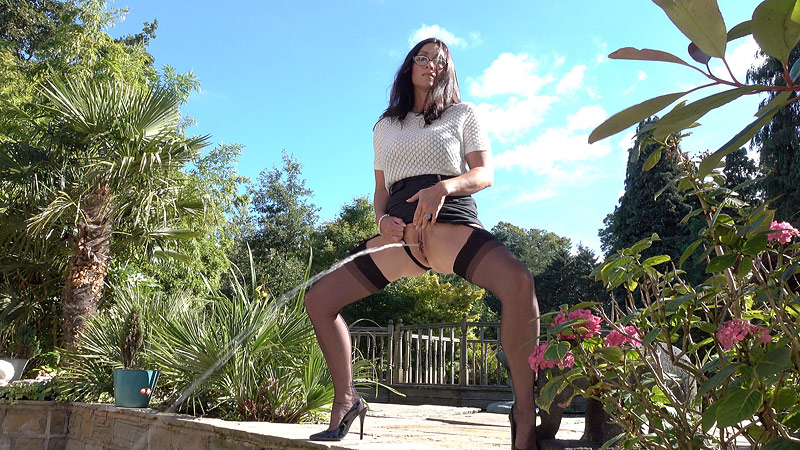 Miss Hybrid free September newsletter watersports in stockings and heels outdoors on the patio.